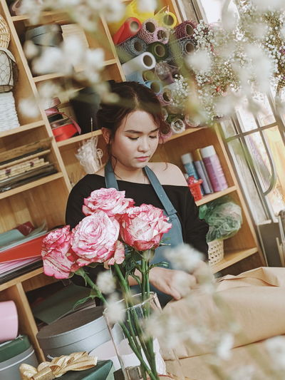 Close-up of flowers against woman working in store