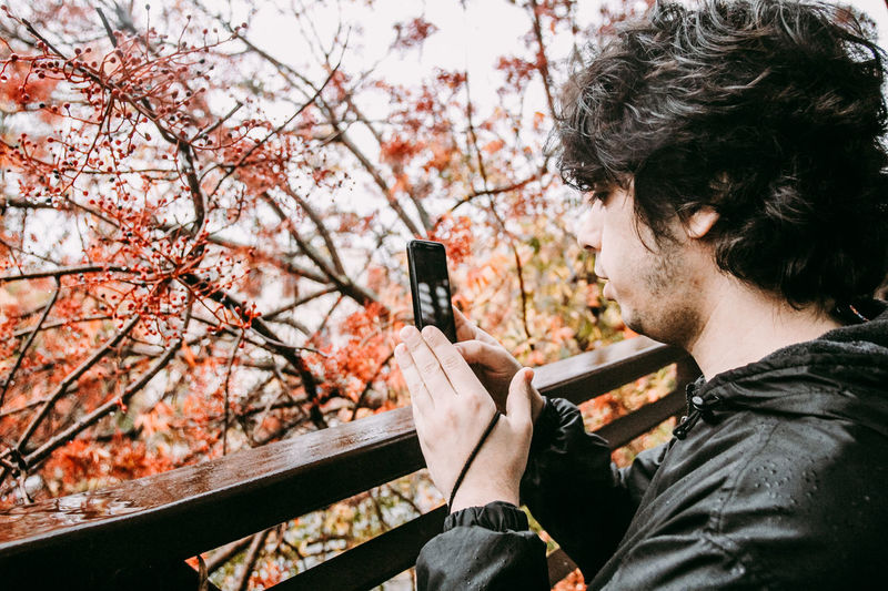 Close-up of young man photographing with mobile phone