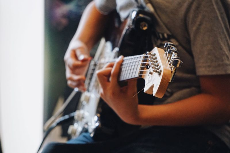 Music Musical Instrument Arts Culture And Entertainment Guitar Playing Musician Lifestyles One Person Leisure Activity Guitarist Skill  Musical Equipment Plucking An Instrument Performance Men Event Indoors  Entertainment Occupation