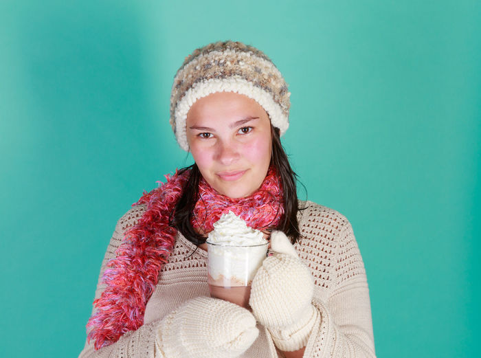 Teen girl in the studio with a cup of hot chocolate wearing a warm hat and gloves Hat Hot Beverage Wintertime Blue Background Clothing Colored Background Gloves Hot Chocolate Indoors  One Person Portrait Studio Shot Teen Girl Teenager Warm Clothing Whipped Cream