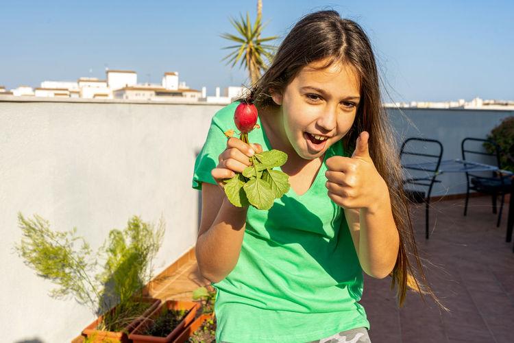 Portrait of girl holding ice cream against sky