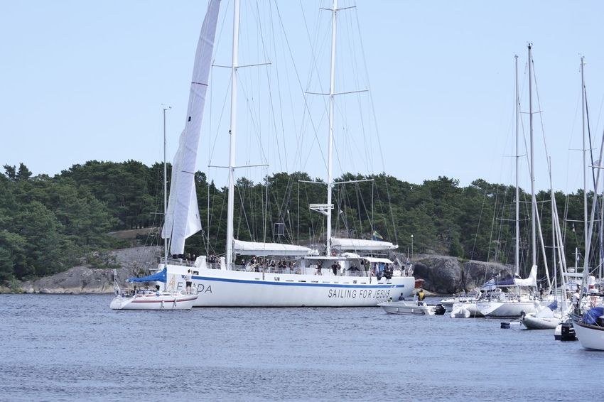 """""""Sailing for Jesus"""" in Sandhamn Blue Boat Calm Clear Sky Day Mast Mode Of Transport Nature Nautical Vessel Ocean Outdoors Sailboat Sailing Boat Sea Sea And Sky Sky Tranquil Scene Tranquility Transportation Unrecognizable People Water Waterfront"""