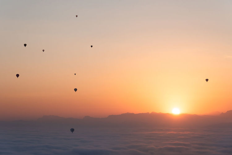 Hot air balloons of the Coupe Aéronautique Gordon Bennett above the sea of fog during sunrise in Bern, Switzerland Bern Adventure Air Vehicle Backgrounds Balloon Beauty In Nature Flying Gordon Bennett Hot Air Balloon Mid-air Minimalism Nature No People Orange Color Outdoors Scenics - Nature Sea Silhouette Sky Sun Sunrise Sunset Tranquil Scene Tranquility Transportation