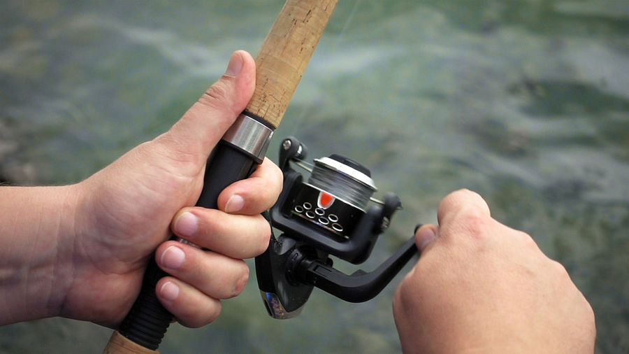Fishing reel Fishing Rod Fishing Tackle Fishing Reel Man Recreation  Active People Activity Authentic Candid Fishing Fishing Line Freshwater Fishing Lake Outdoors Real Life Real People River Sea Spinning Spinning Rod Spring Springtime Summer Water Waterfront