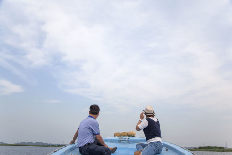 Rear View Of Men Sitting On Boat In River Against Cloudy Sky