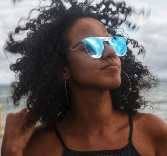 Thoughtful young woman wearing sunglasses at beach