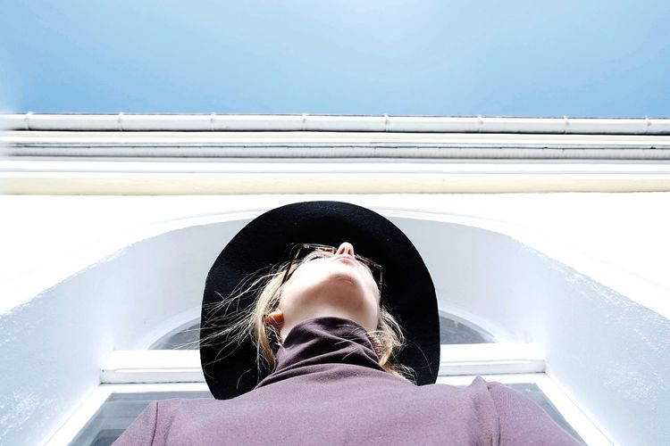 Low Angle View Of Woman Standing By Building Against Sky