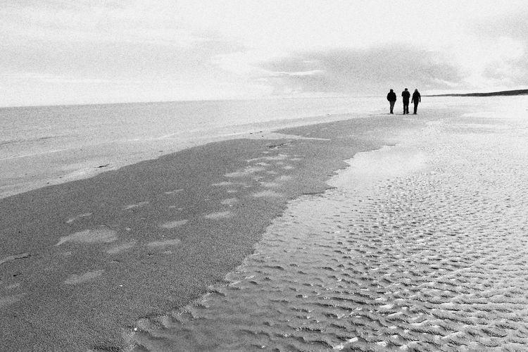Low tide with people Nova Scotia, Canada Shoreline And People Three People Walking Along Beach Black And White Beach Scene Calm Before The Storm Moody Beach Silhouette Of People Strolling Along The Beach