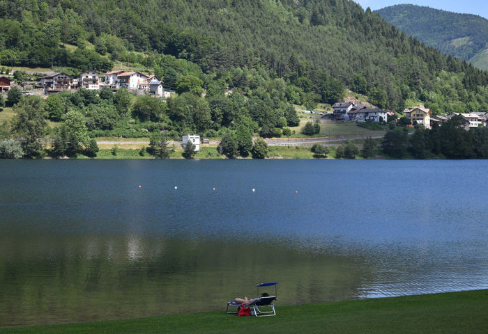 View of the artificial Lake of Piazze in Trentino, Italy, with grassy shore and early tourist relaxing. EyeEmNewHere Holidays Holidays ☀ Relaxing Tourist Travel Trentino  Artificial Lake Beauty In Nature Grass Green Color Incidental People Italy Italy❤️ Lake Mountain Nature Outdoors Peaceful Piazze Qiuet Relax Scenics - Nature Summer Water The Traveler - 2018 EyeEm Awards