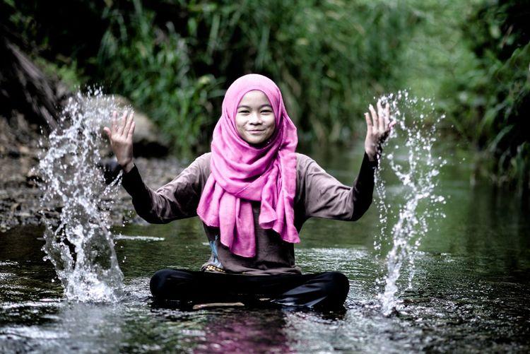 View of happy girl splashing water