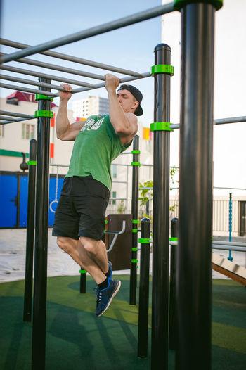 Muscular man exercising against sky at park
