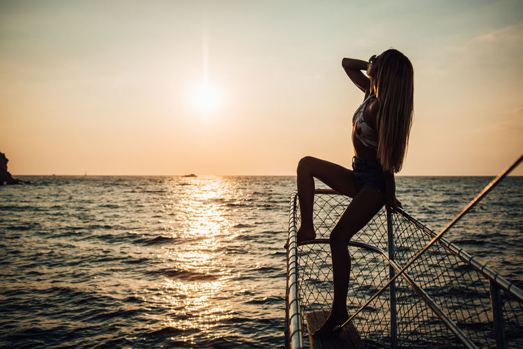 Water Sea Sky Sunset Horizon Real People Beauty In Nature Leisure Activity Horizon Over Water Lifestyles One Person Scenics - Nature Nature Sun Activity Adult Tranquility Women Sunlight Outdoors Wireless Technology