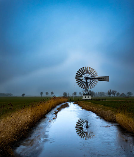 To me this photograph reminds of a painting my grandmother made of a windmill, standing nice and quiet. When she made that she gave it as present to my other grandmother. With the intention if she would die one day, i would get it. A reminder on how she saw the world. (Taken at Baard, Friesland) Americana Frozen Gold Green Netherlands Reflection Trees Beauty In Nature Cloud - Sky Day Flatland Friesland Landscape Mist Nature No People EyeEmNewHere Outdoors Scenics Sky Steel Structure  Traditional Windmill Water Wind Turbine Windmill