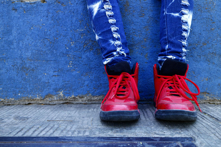 red rubber shoes, blue long pants and blue wall Foot Feet Body Part Rubber Shoes Sole Basketball Low Section Blue Red Shoe Standing Men Close-up Footwear Ground Shoelace Canvas Shoe