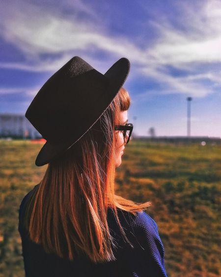 Portrait of woman wearing hat standing on field against sky