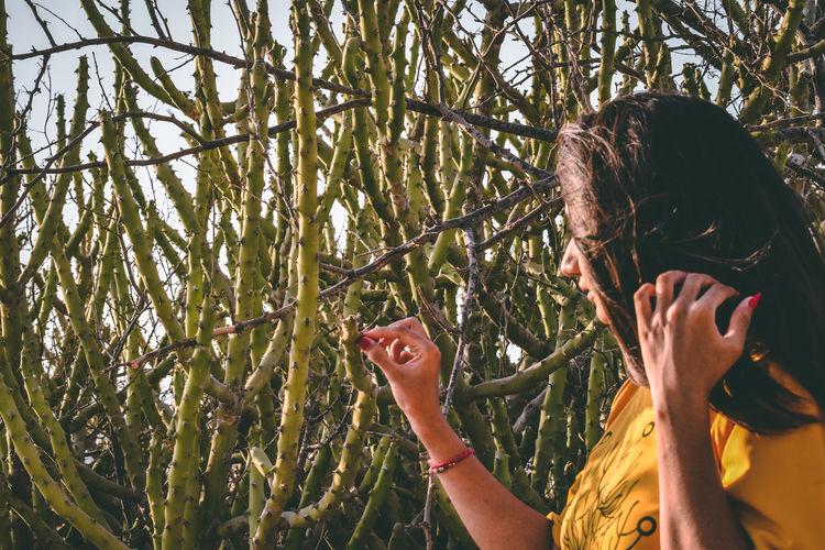 Portrait of woman holding plants against trees