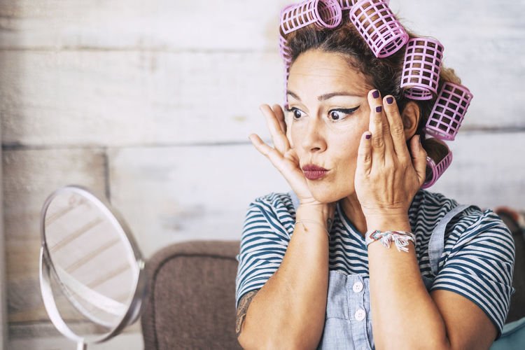 Woman wearing hair curlers at home