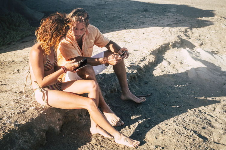 High angle view of couple using mobile phone while sitting on land at beach