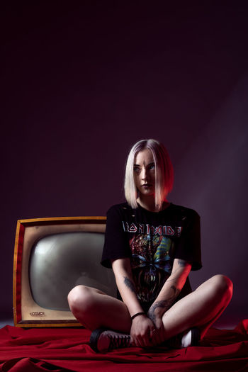 Portrait of a young woman sitting against black background