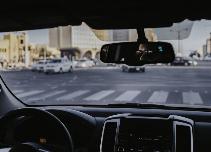 Man wearing sunglasses driving car reflecting in mirror