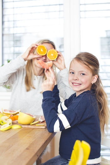 Portrait Of Girl With Mother Holding Orange Fruit At Home