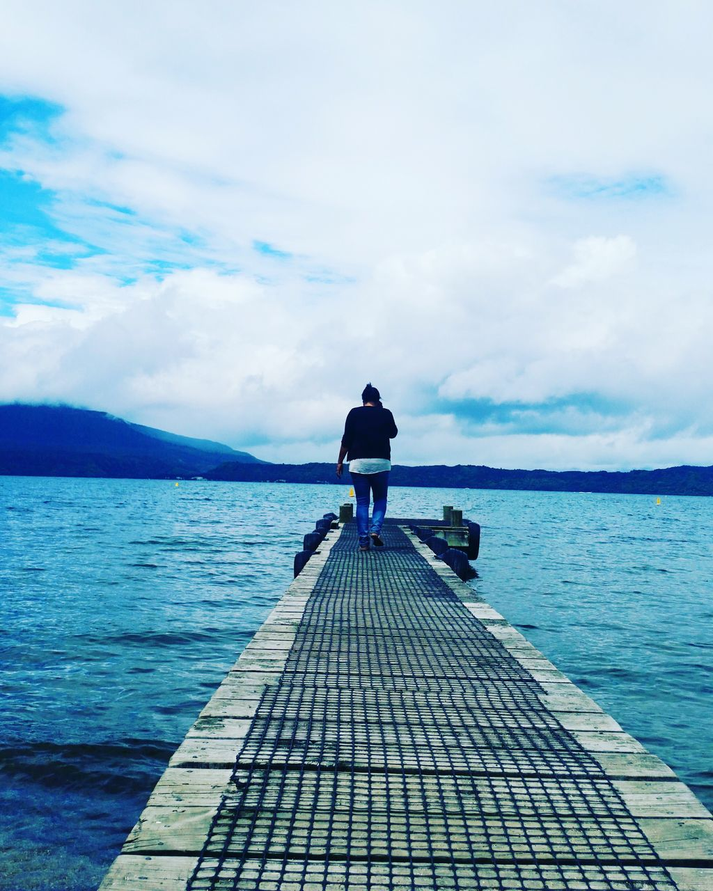 full length, rear view, sky, one person, water, cloud - sky, real people, sea, tranquil scene, standing, jetty, day, nature, outdoors, scenics, beauty in nature, tranquility, leisure activity, horizon over water, wood paneling, adult, people