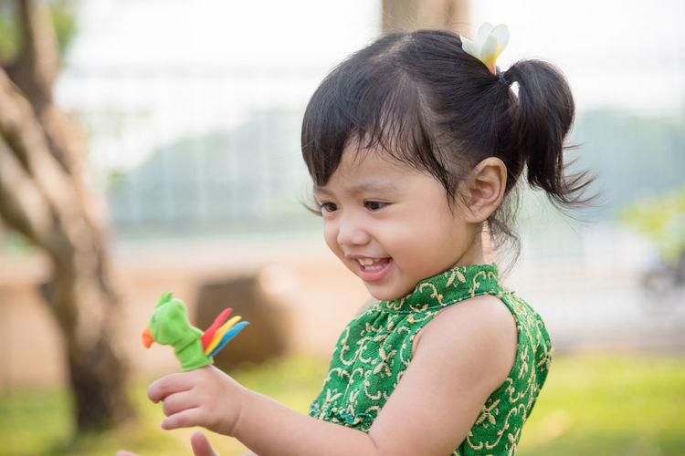Smiling girl holding toy in finger against trees