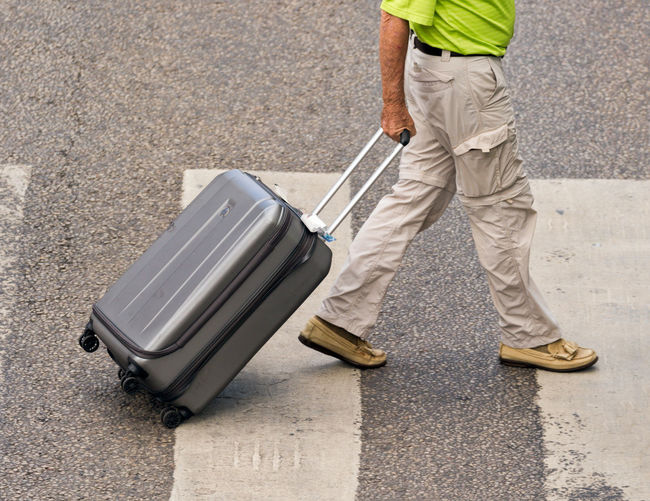 Low section of man with suitcase on street