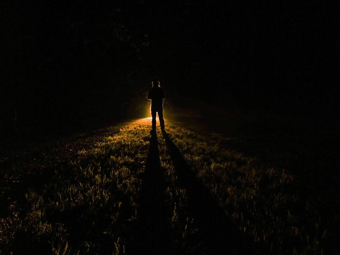 Rear view of man standing on grass with illuminated light at night