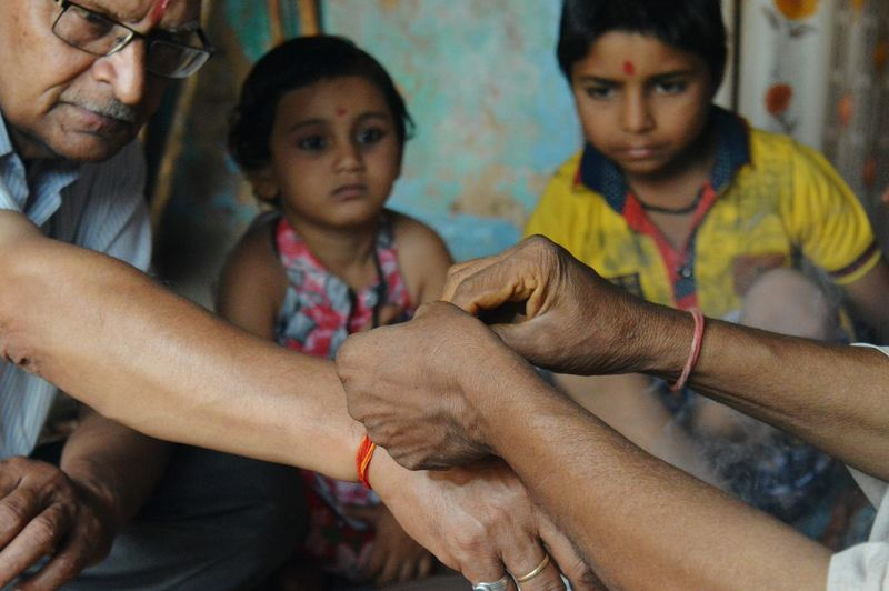 Cropped Image Of Person Tying Thread To Man Hand While Children Looking At Home