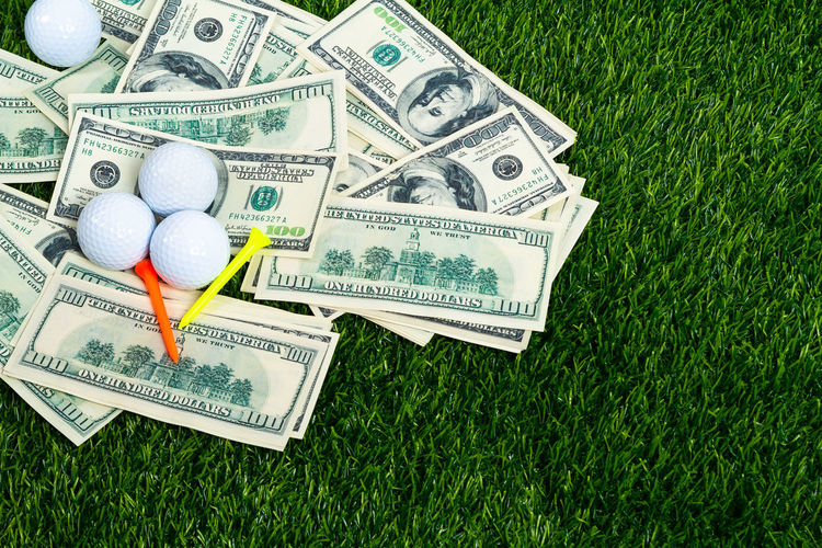 High angle view of paper currency with golf ball on land