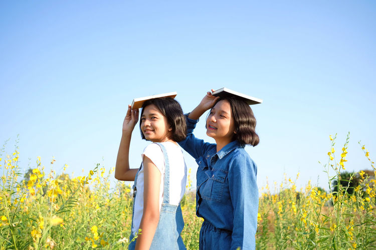 Smiling teenage girls carrying book on head