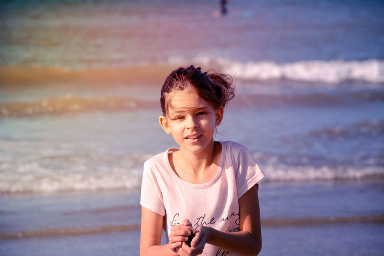 Portrait of smiling girl against sea at beach
