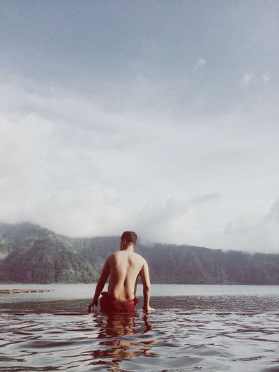 Rear view of shirtless man in water against sky