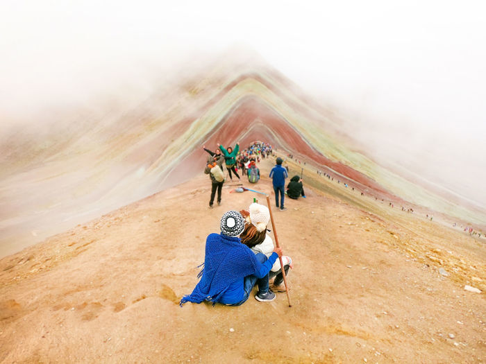 Rear view of people sitting on multi colored mountain