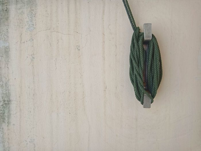 Close-up of rope hanging against wall