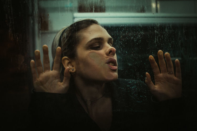 Close-up of woman by window