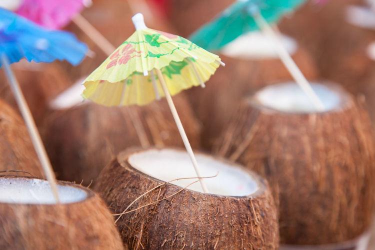 Close-up of coconuts with drink umbrellas