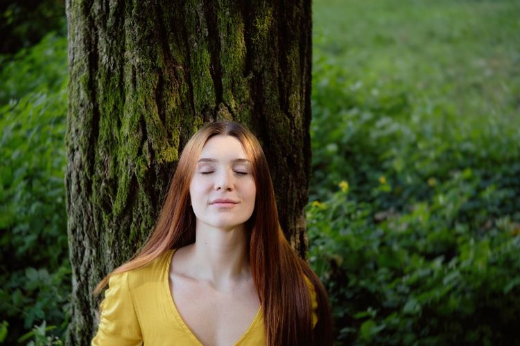 Young woman with eyes closed standing by tree trunk