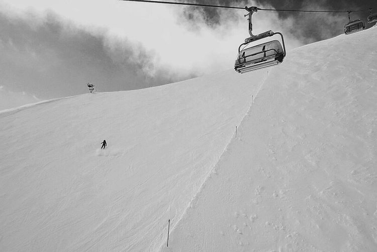 Low angle view of ski lift over snow covered mountain