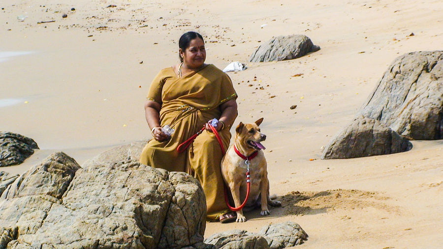 Overweight woman with dog sitting on rock at beach during sunny day