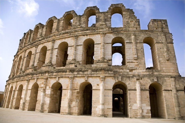 Coliseum in El Jem. Tunis. Africa; Antique; Arch; Archeology; Architecture; Blue; Coliseum; Durable; Historical; History; Landmark; Old; Perpetual; Ruin; Travel; Tunis; Tunisia; Vacation Amphitheater Ancient Ancient Civilization Ancient History Arch Archaeology Arched Architectural Column Architecture Arts Culture And Entertainment Building Exterior Built Structure Day History Low Angle View Nature No People Old Ruin Outdoors Ruined Sky The Past Tourism Travel Travel Destinations