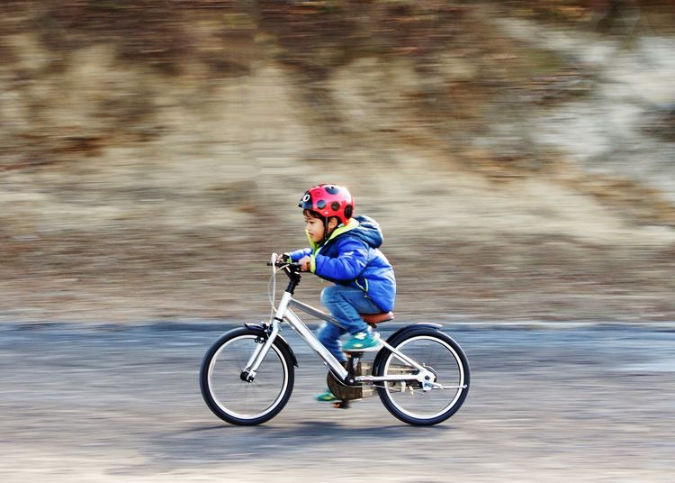 Panning shot of a boy riding a bicycle Activity Active Fun Youth Bicycle Helmet Full Length Transportation Sport Cycling One Person Headwear Motion Sports Helmet Cycling Helmet Ride Riding Sports Equipment Mode Of Transportation Child Activity Outdoors