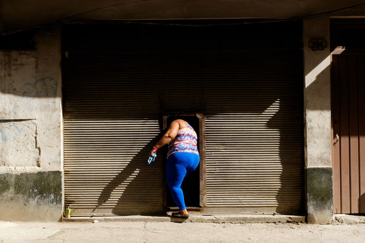 Portrait of woman standing against closed shutter