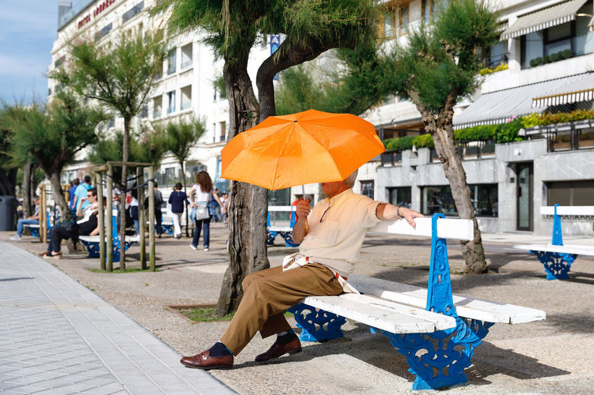 San Sebastian, Spain EyeEm Best Shots SPAIN Travel Travel Photography Architecture Building Exterior Built Structure City Day Footpath Full Length Incidental People Lifestyles Men Nature One Person Outdoors Plant Protection Real People Sitting Social Issues Street Travel Destinations Umbrella