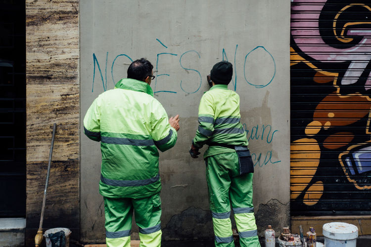 Rear view of men making graffiti on concrete wall