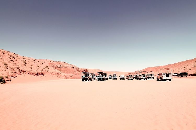 Cars parked at antelope canyon against clear sky