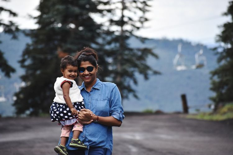 Portrait of smiling woman holding daughter while standing on road