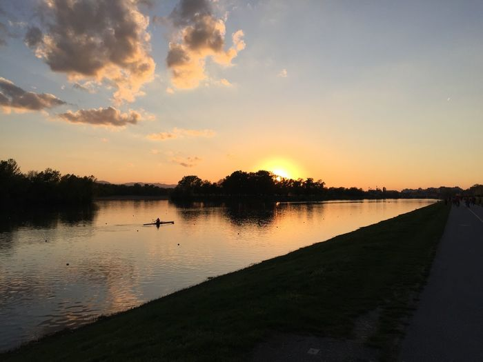 Person kayaking on river at dusk