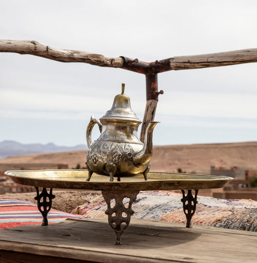 Sky Nature Architecture Focus On Foreground Day No People Art And Craft Outdoors Representation Built Structure Metal Wood - Material Close-up Old Creativity Antique Teapot Silver Colored Ksar Ait Ben Hadu Table Tea View